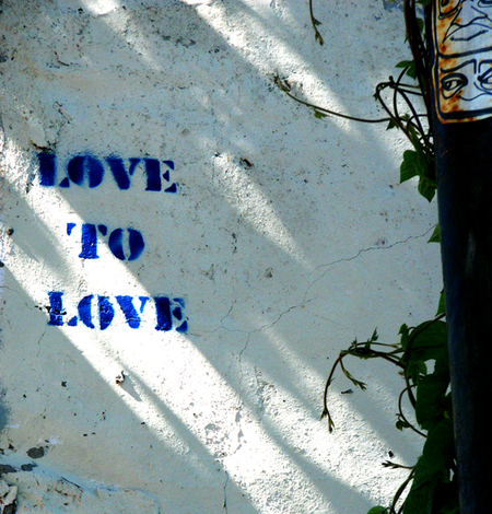 Graffitied words on a peeling wall that says Love to Love